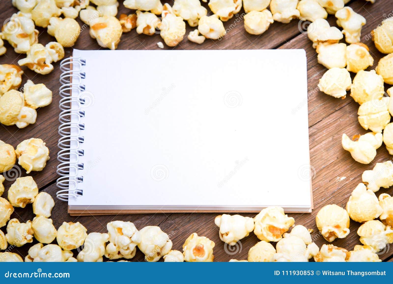 一个碗玉米花和笔记本在一张木桌上