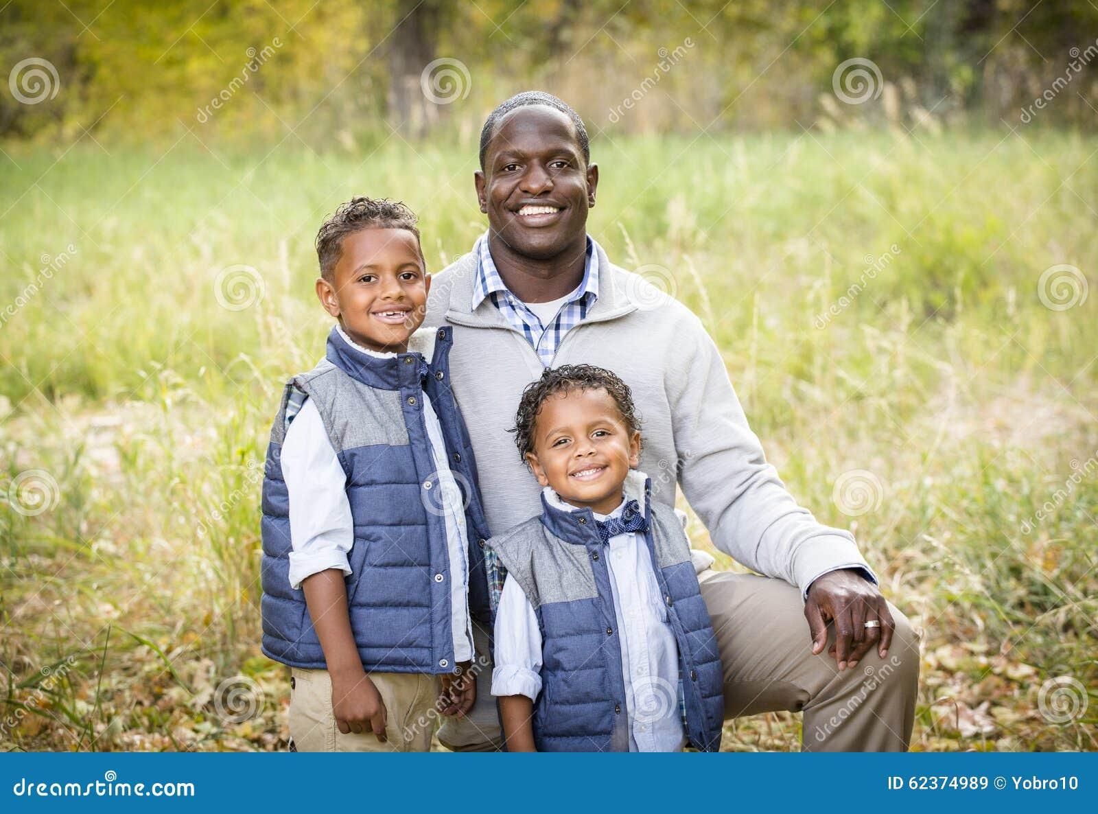 一个种族地不同的父亲的室外画象有他的两个儿子的