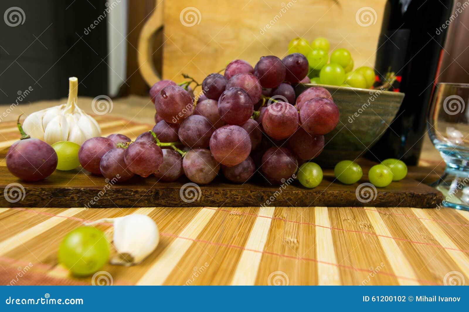 一个红色和黄色麝香葡萄的侧视图上色了葡萄、瓶酒,大蒜和一块玻璃在一个木板-静物画