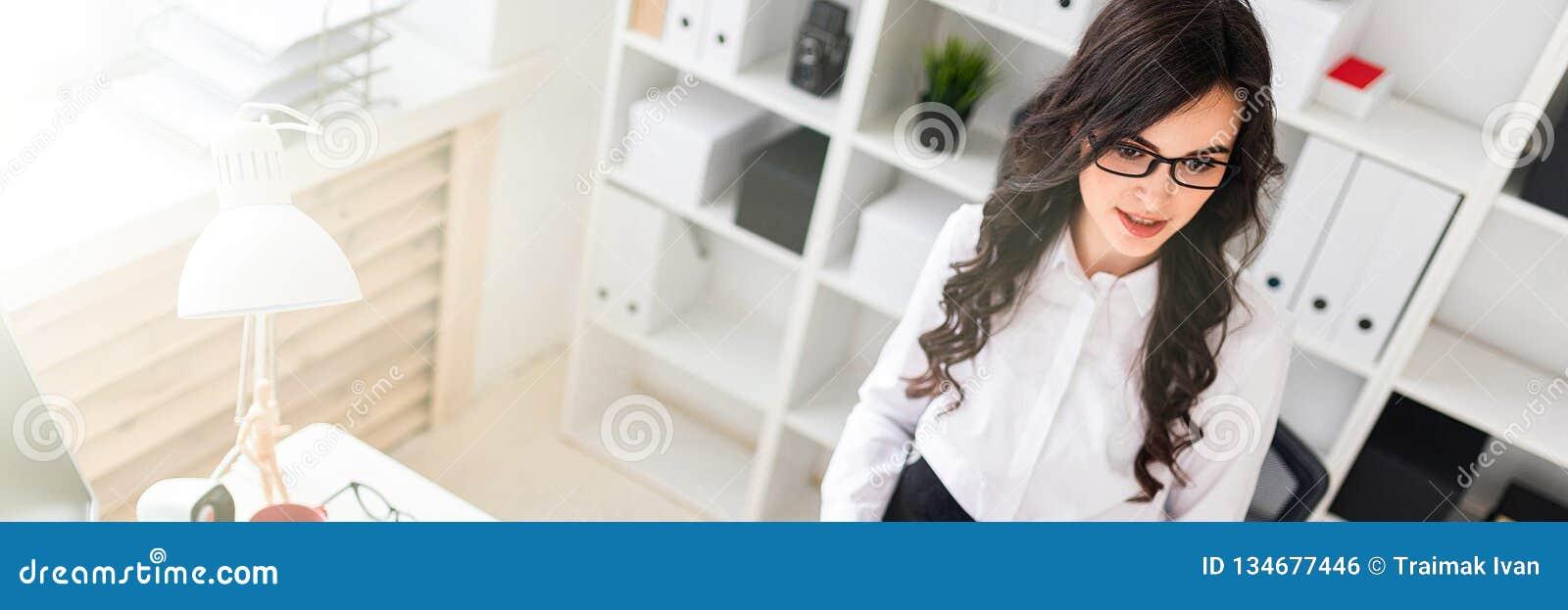 一个美丽的女孩在办公桌附近在她的手上站立并且拿着笔记和铅笔的板料