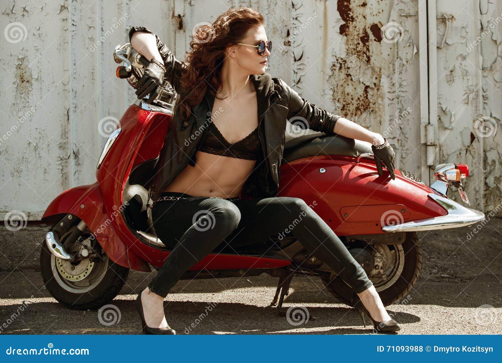 一个美丽的女孩的画象皮夹克的,胸罩和玻璃临近红色摩托车