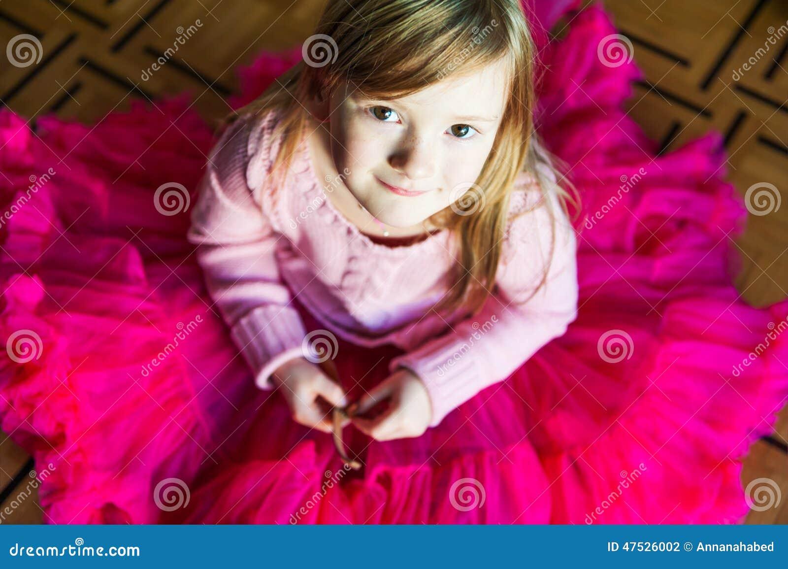 一个美丽的小女孩的室内画象坐在一件明亮的桃红色裙子芭蕾舞短裙的一图片