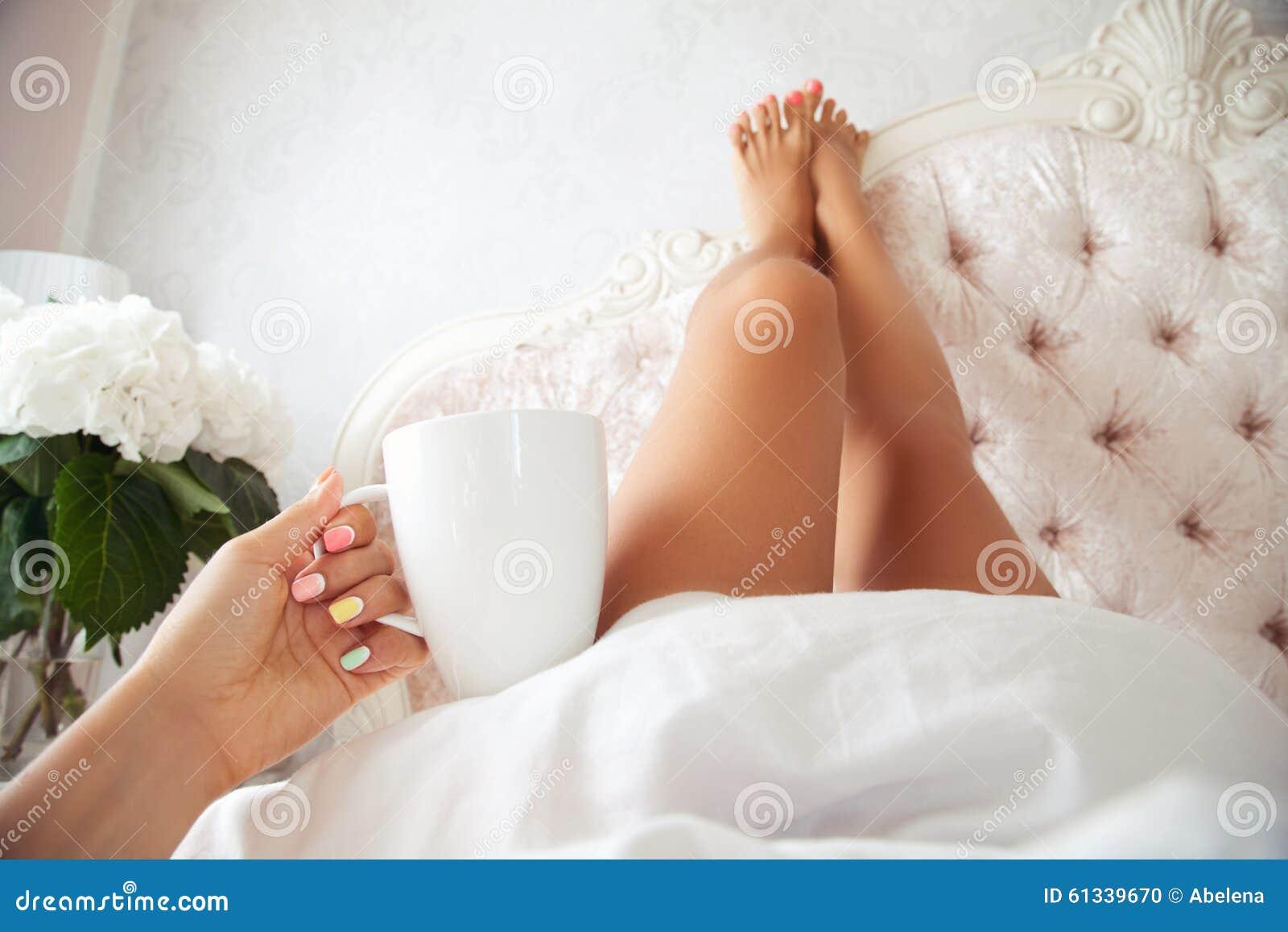 妇女软的照片有咖啡的在手中和腿在卧室提高了高说谎在床上.