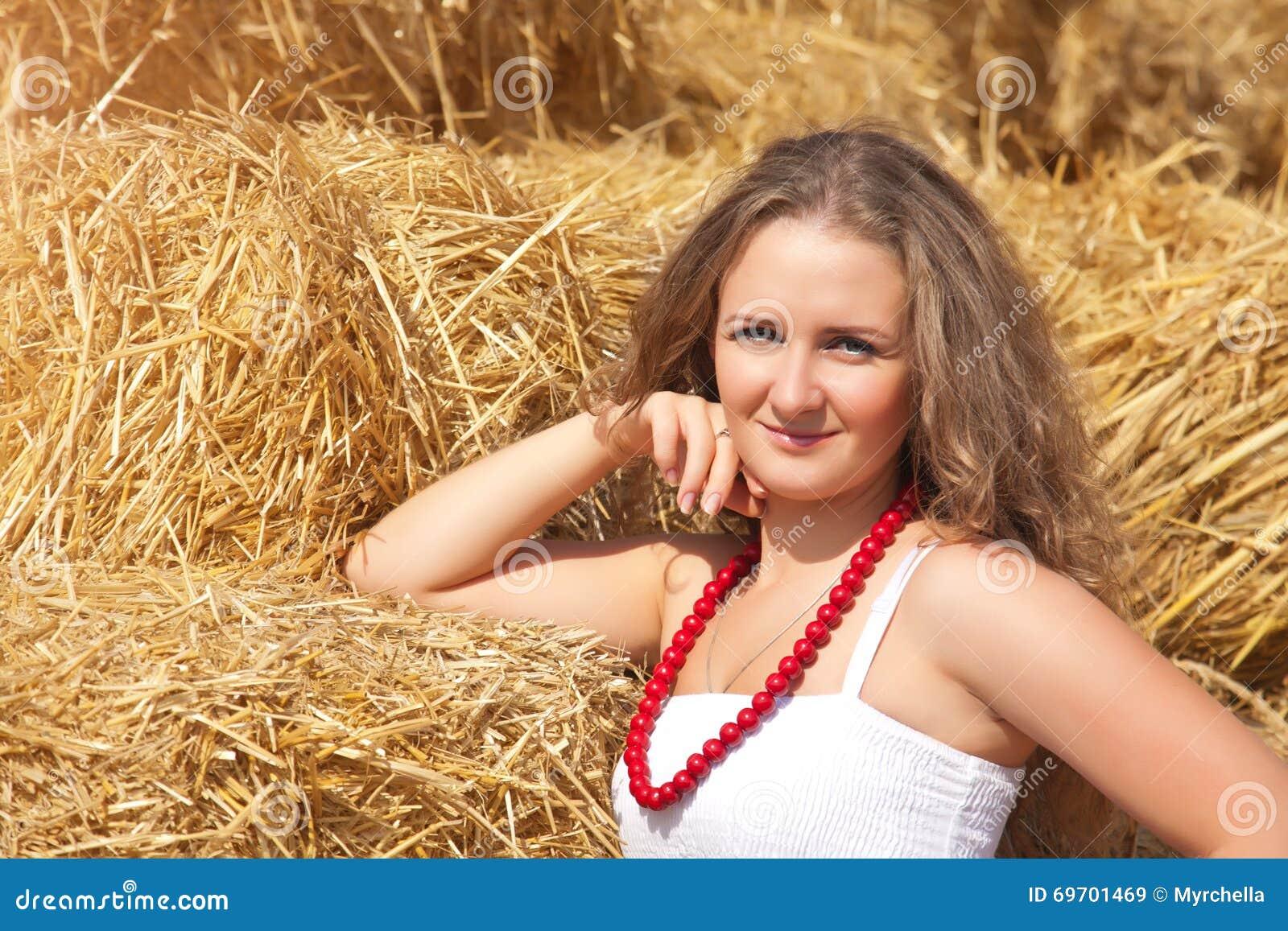 一个美丽的少妇的画象在乡村模式穿戴了在干草背景.