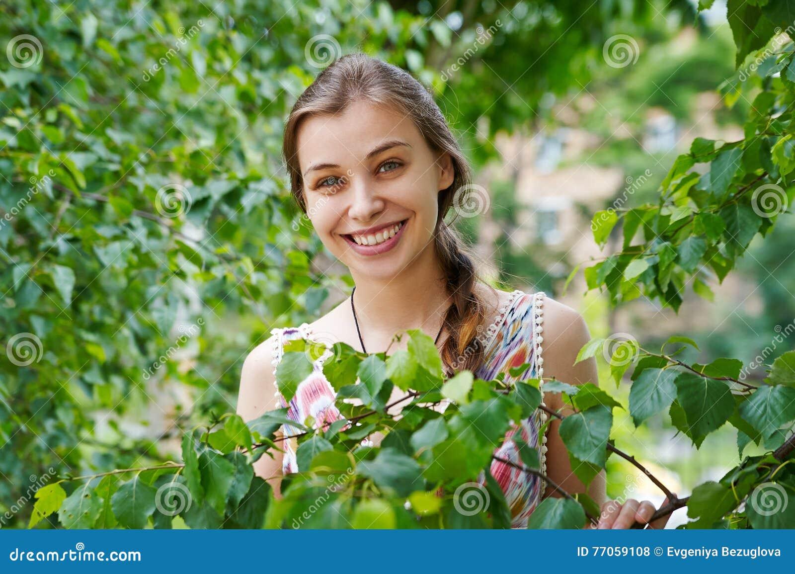 一个美丽的少妇的画象绿色叶子背景的