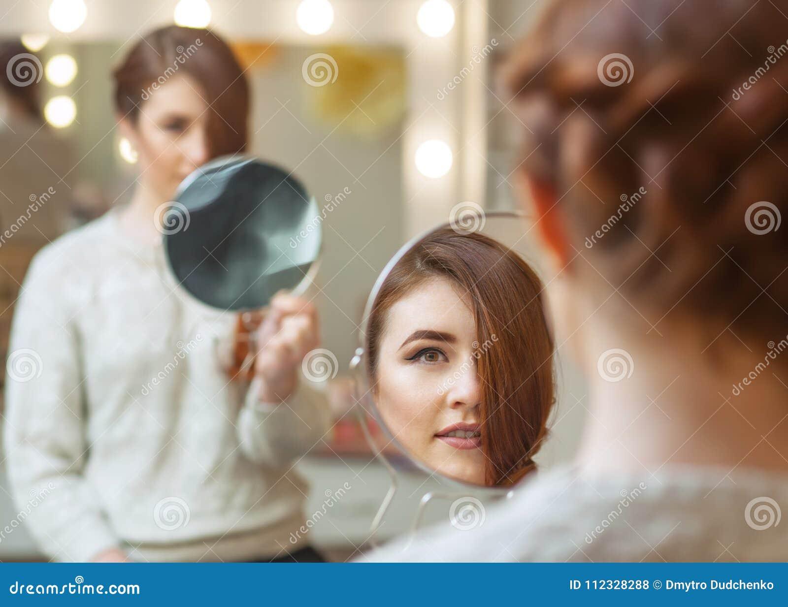 一个美丽的红发女孩的画象有长的头发的,在美容院的镜子看