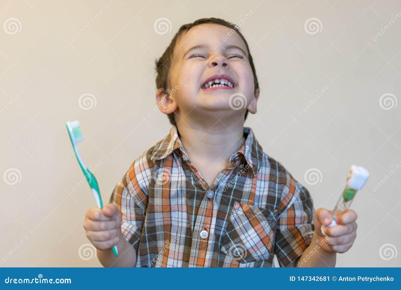 一个美丽的逗人喜爱的白种人白肤金发的男孩的画象有牙刷的 小男孩掠过的牙和微笑,当照料时