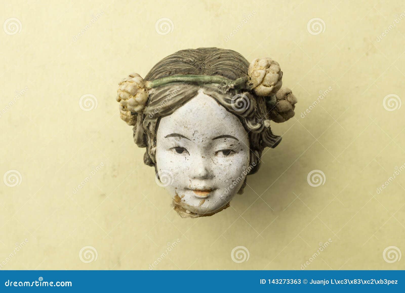 一个老损坏的瓷中国玩偶头的细节