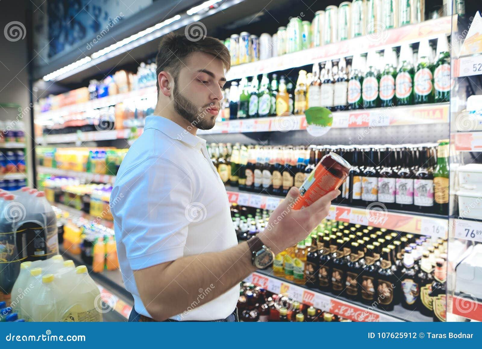 一个英俊的有胡子的人在超级市场选择啤酒 买家在超级市场买酒精
