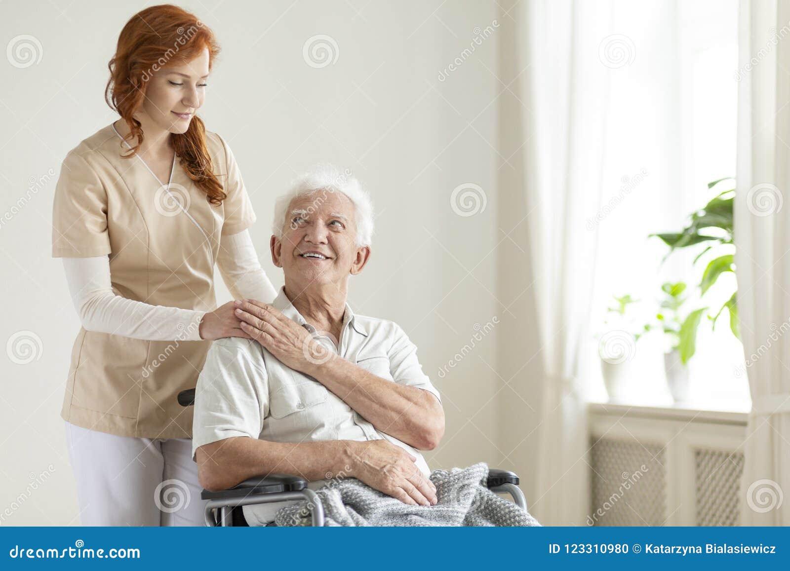 一个轮椅和友好的照料者的微笑的年长人a的