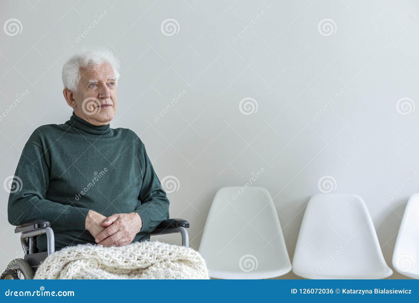 一个轮椅的被麻痹的人在一间候诊室在医院