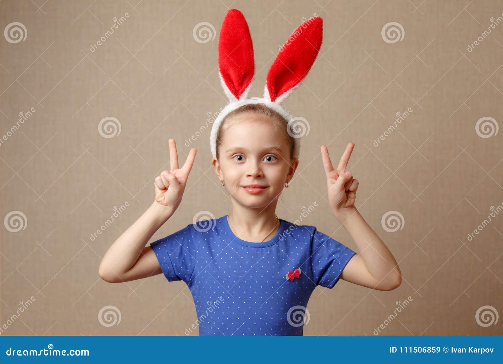 一个逗人喜爱的小女孩的画象在复活节兔子耳朵穿戴了