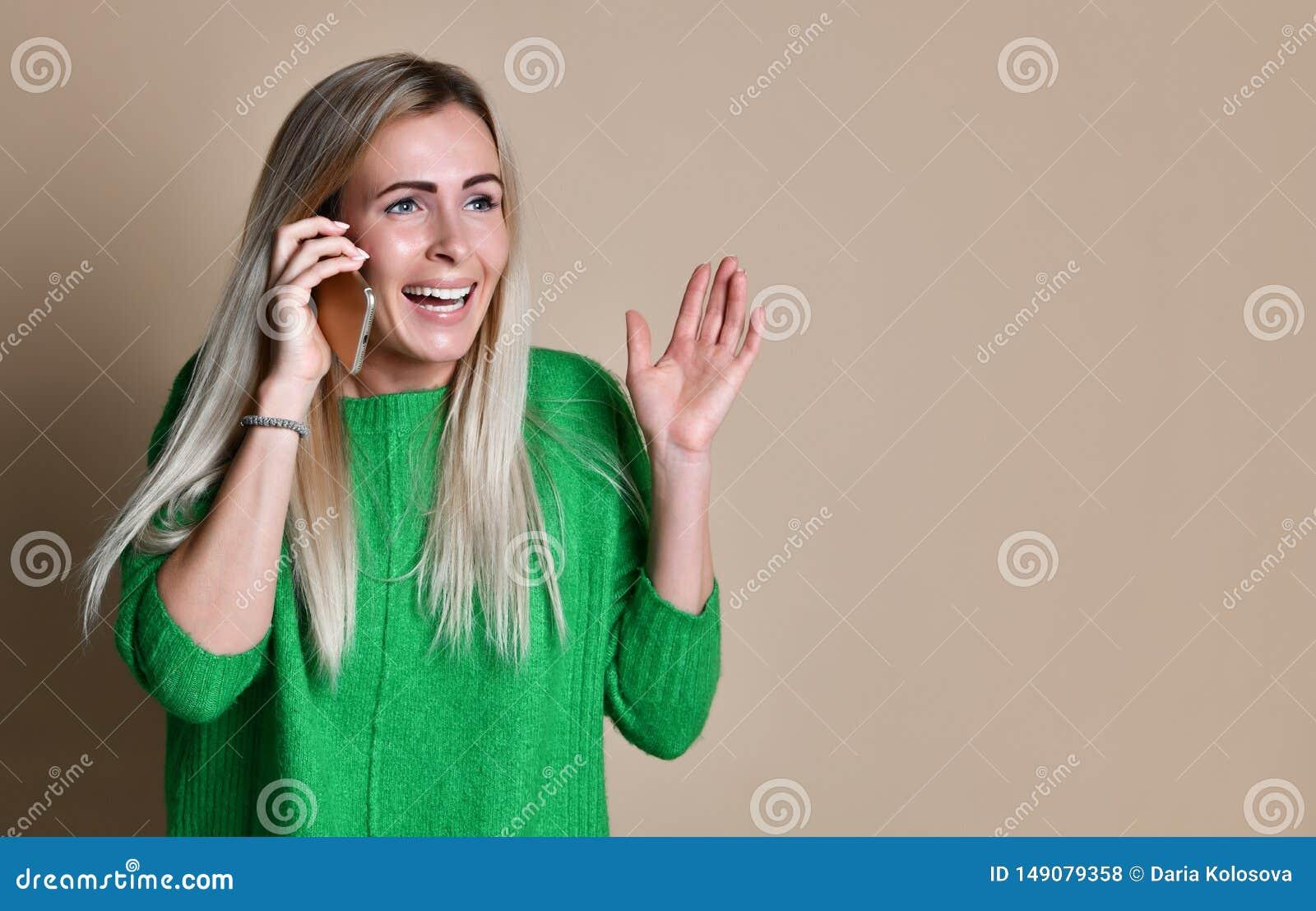 一个逗人喜爱的愉快的女孩的画象谈话在手机和笑