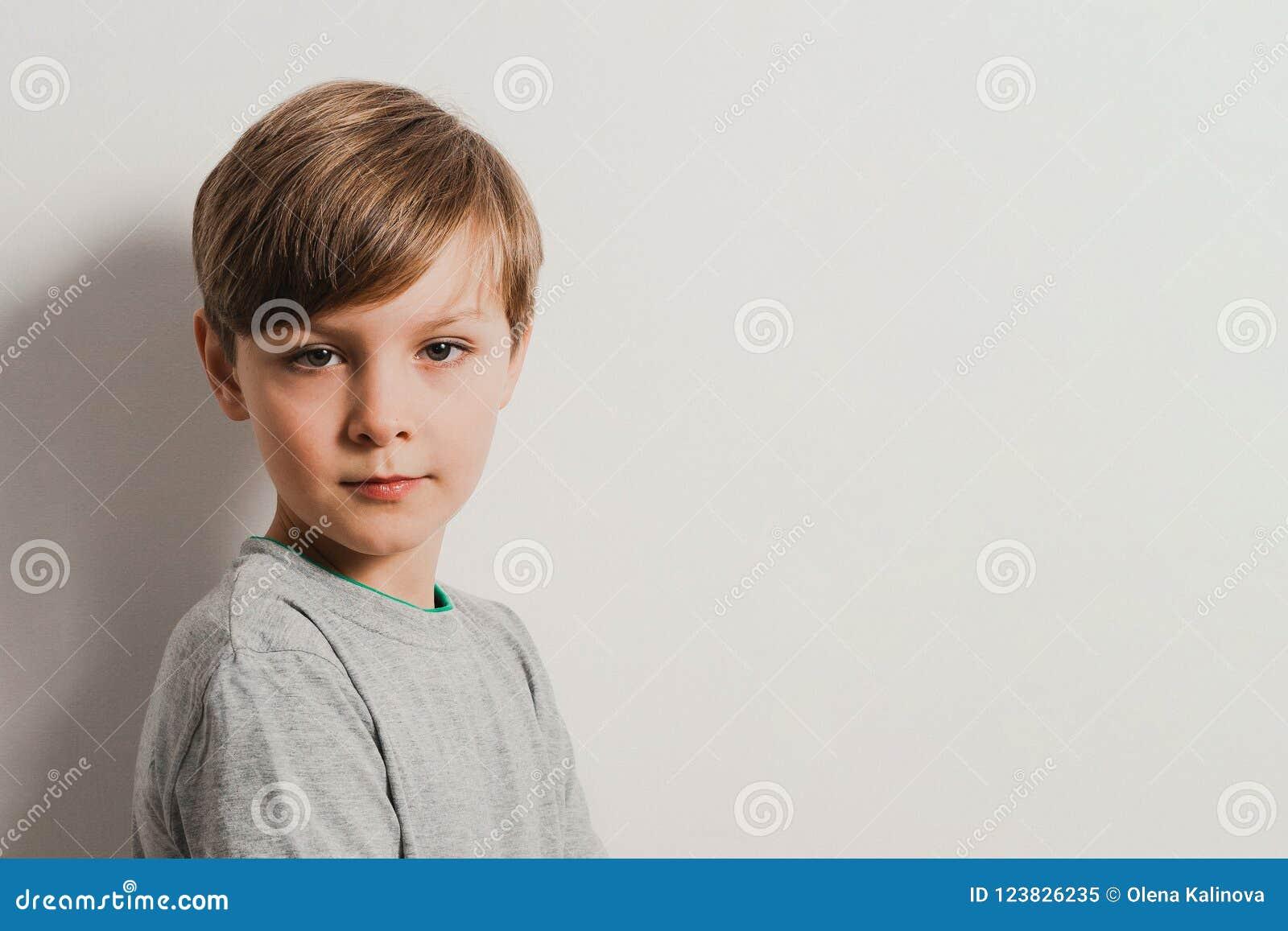 一个逗人喜爱的男孩的画象一件灰色衬衣的,由白色墙壁