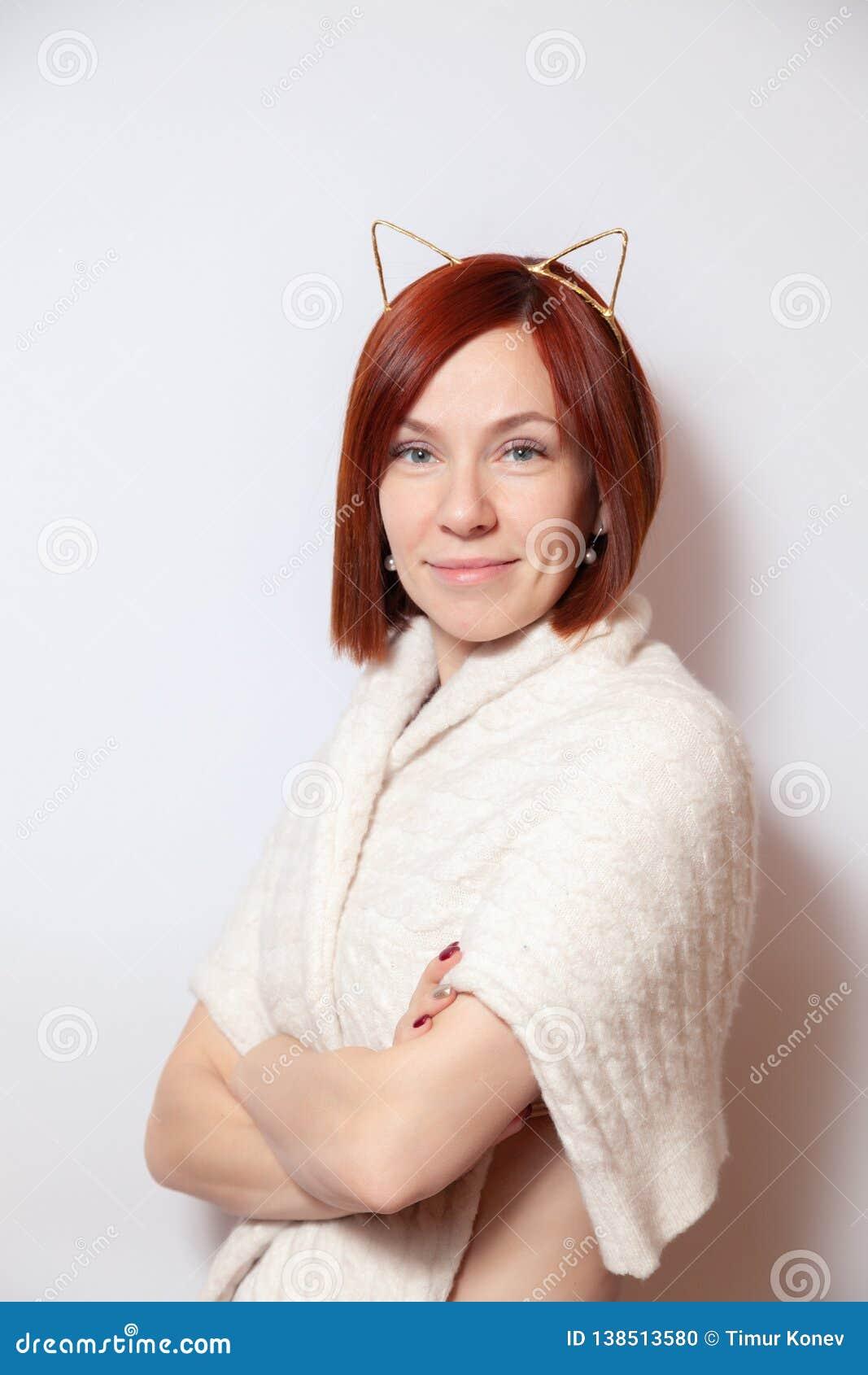 一个金外缘的与耳朵,在看照相机的白色背景的被编织的米黄毛线衣年轻微笑的红发女孩 电缆太选择许多的概念照片适当的usb
