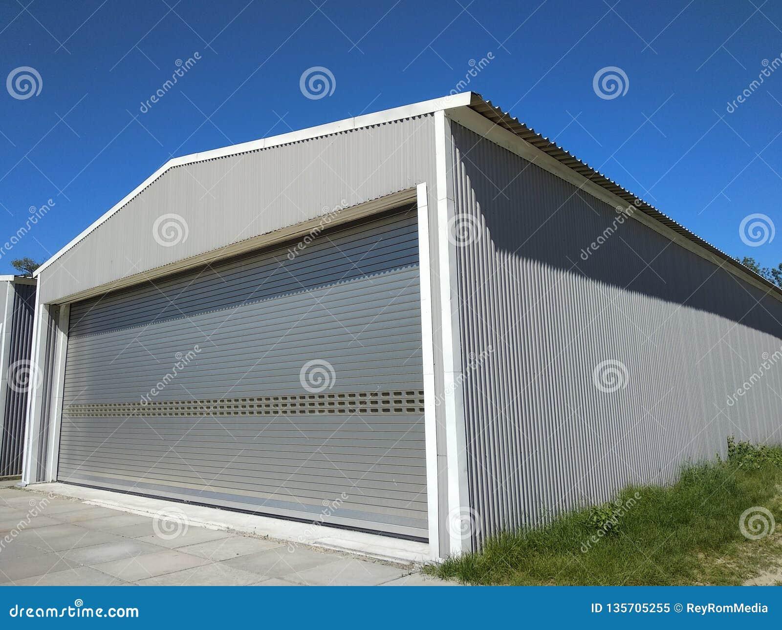 一个金属飞机棚外部制造或存贮的 与闭合的滚动的门的侧视图车库与具体封锁的流程