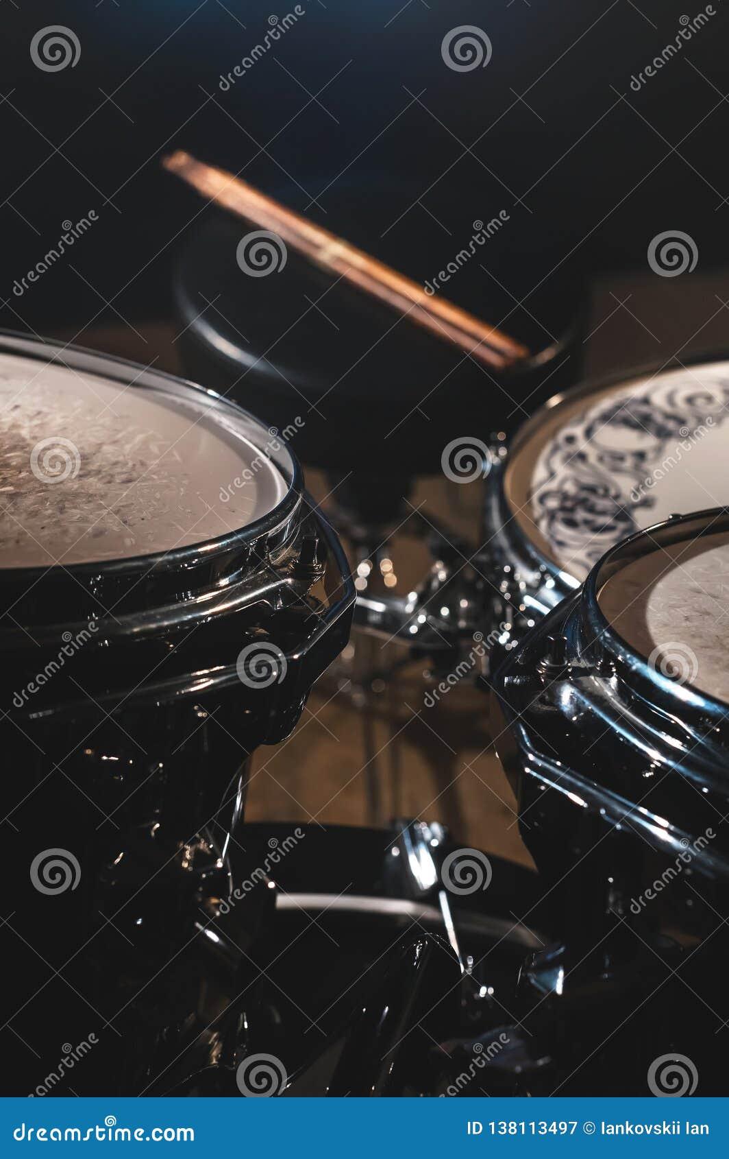 一个鼓集合和鼓槌的特写镜头视图在一个黑暗的演播室 与镀铬物修剪的布莱克的鼓桶 概念的活