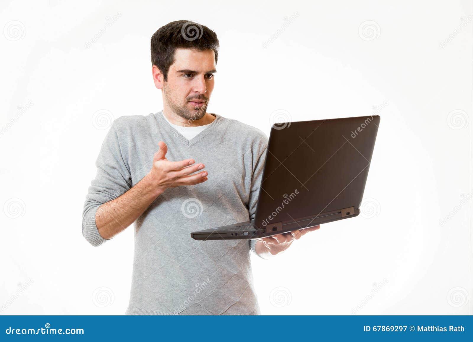 一个年轻人看起来怀疑在他的膝上型计算机
