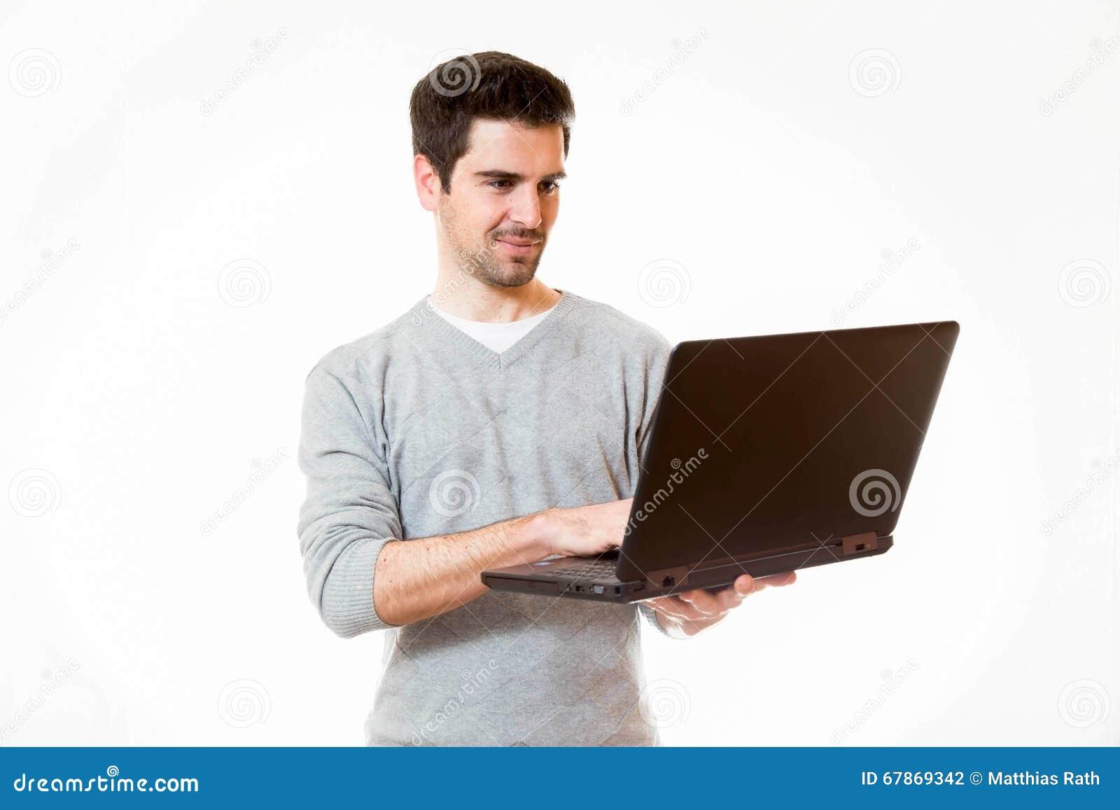 一个年轻人研究膝上型计算机,当站立时