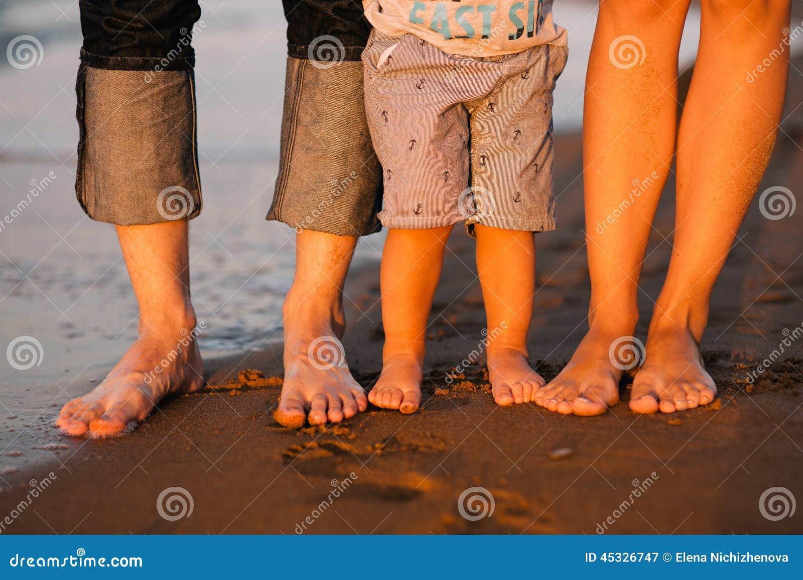 一个年轻家庭的脚在海的靠岸