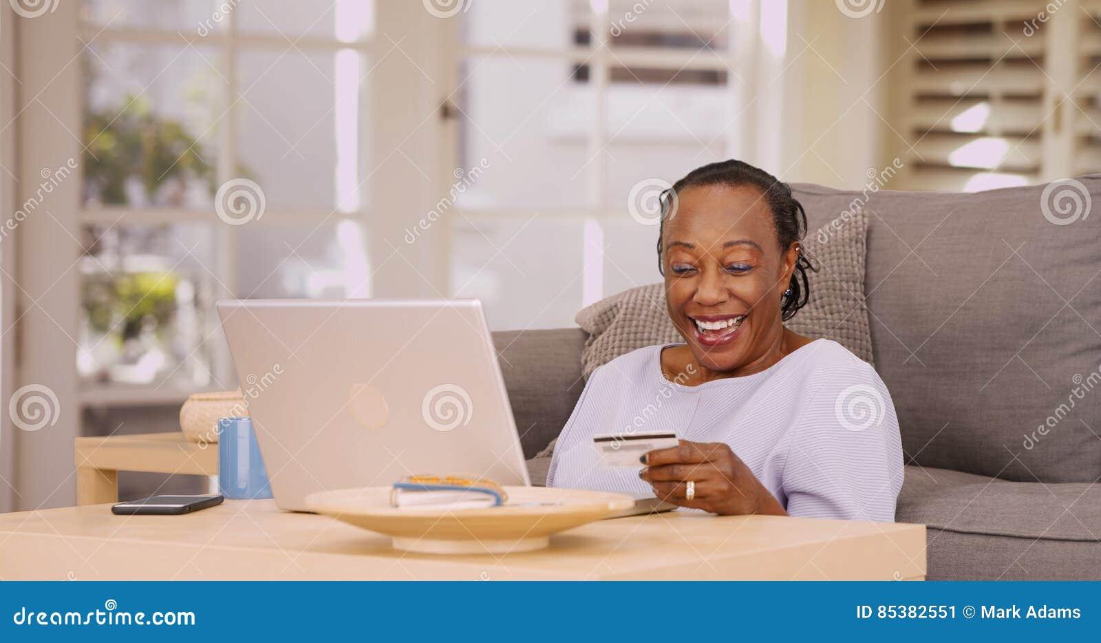 一个更老的黑人妇女付她在她的膝上型计算机的帐单