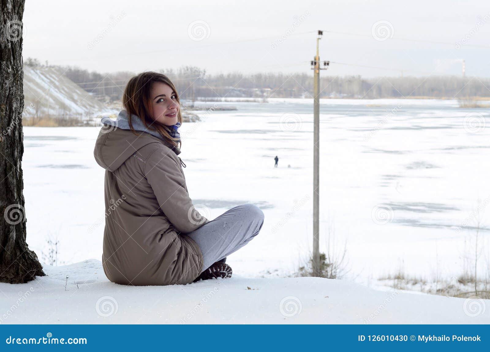 一件棕色外套的一个年轻白种人女孩在峭壁附近在天际线的背景中坐在天空之间的