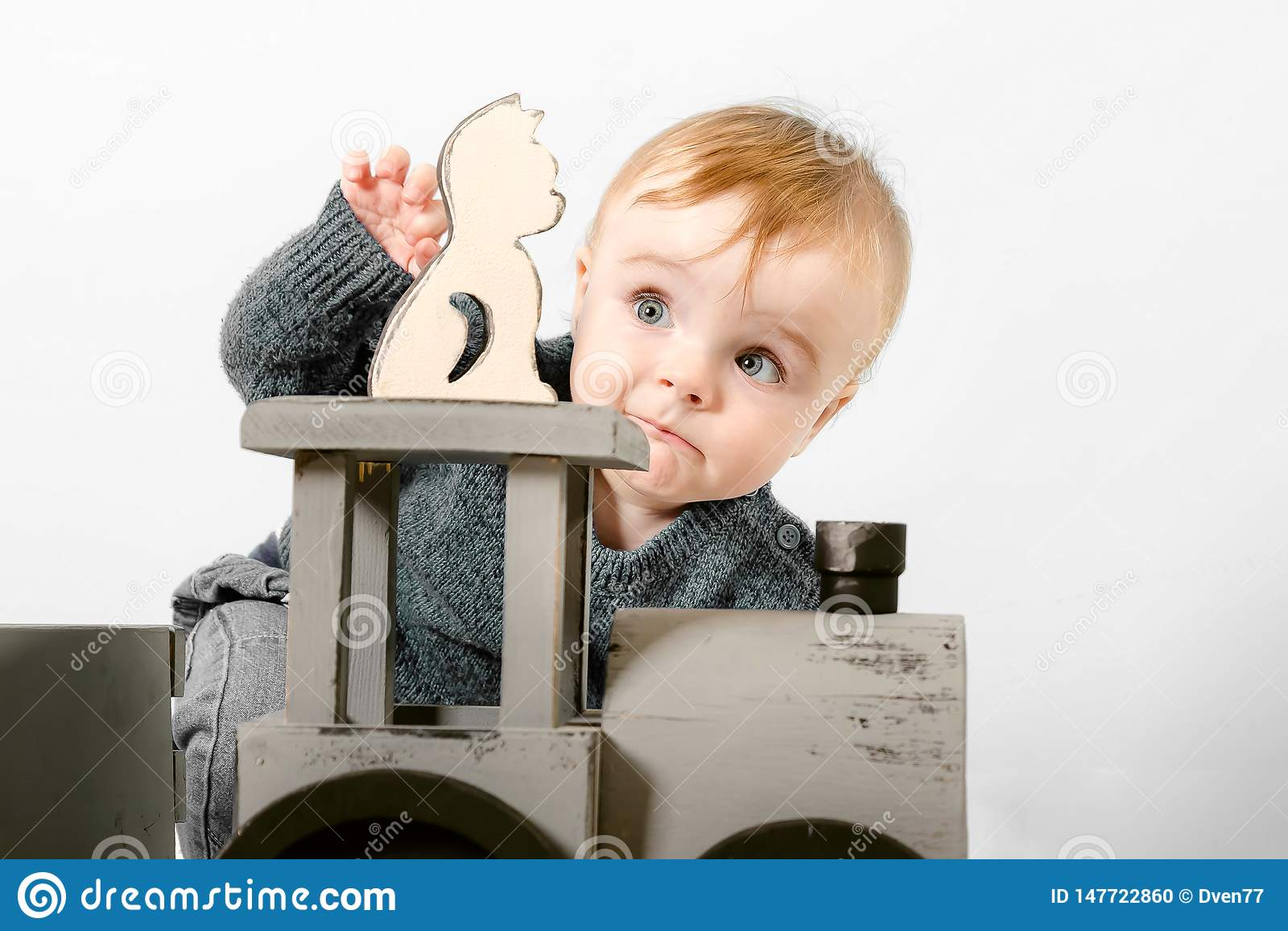 一件灰色毛线衣的惊奇的一岁的孩子演奏木玩具 白色背景的白肤金发的男婴 ??