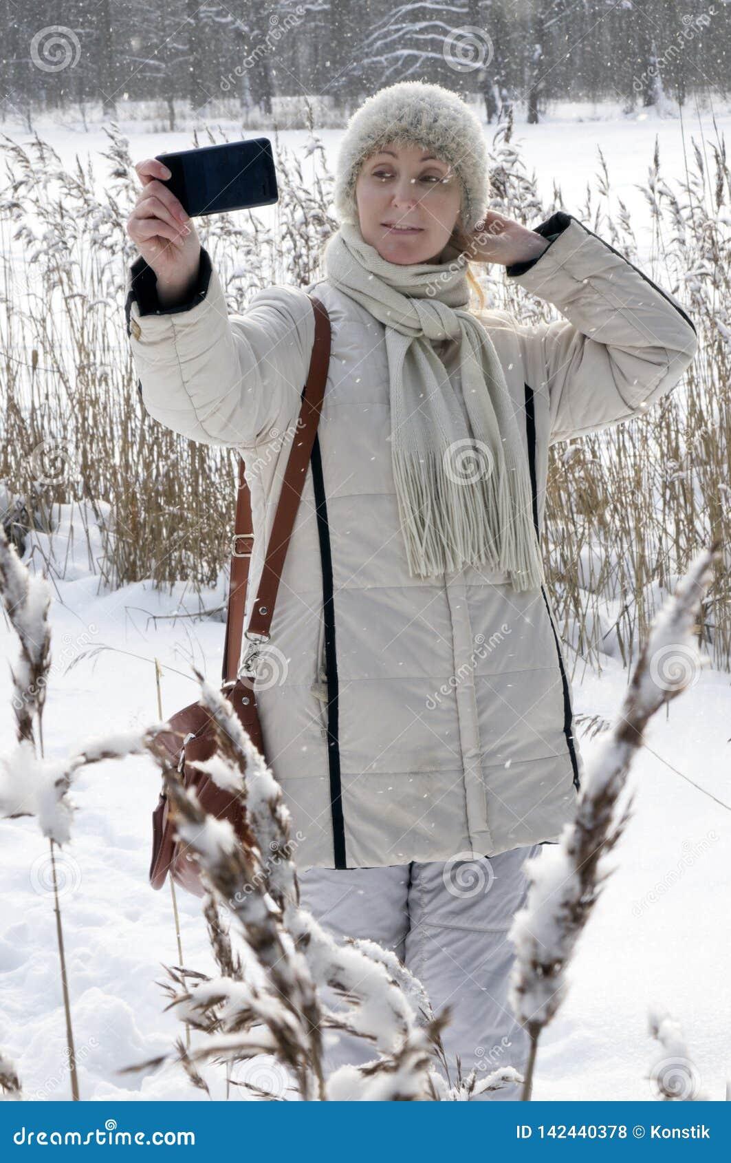 一件白色夹克的年轻女人在冬天森林湖的海岸做一selfie