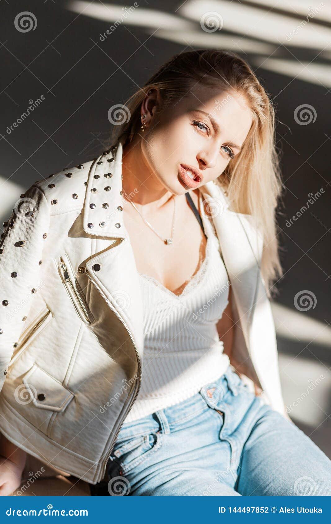 一件白色时髦的T恤杉的俏丽的性感的年轻白肤金发的妇女在葡萄酒牛仔裤的一件时兴的夏天夹克享受明媚的阳光