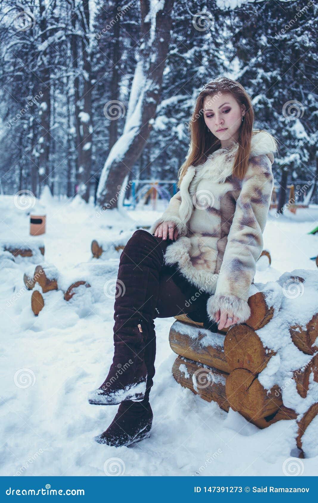 一件米黄短的外套的美女有流动的头发的坐一个木制框架