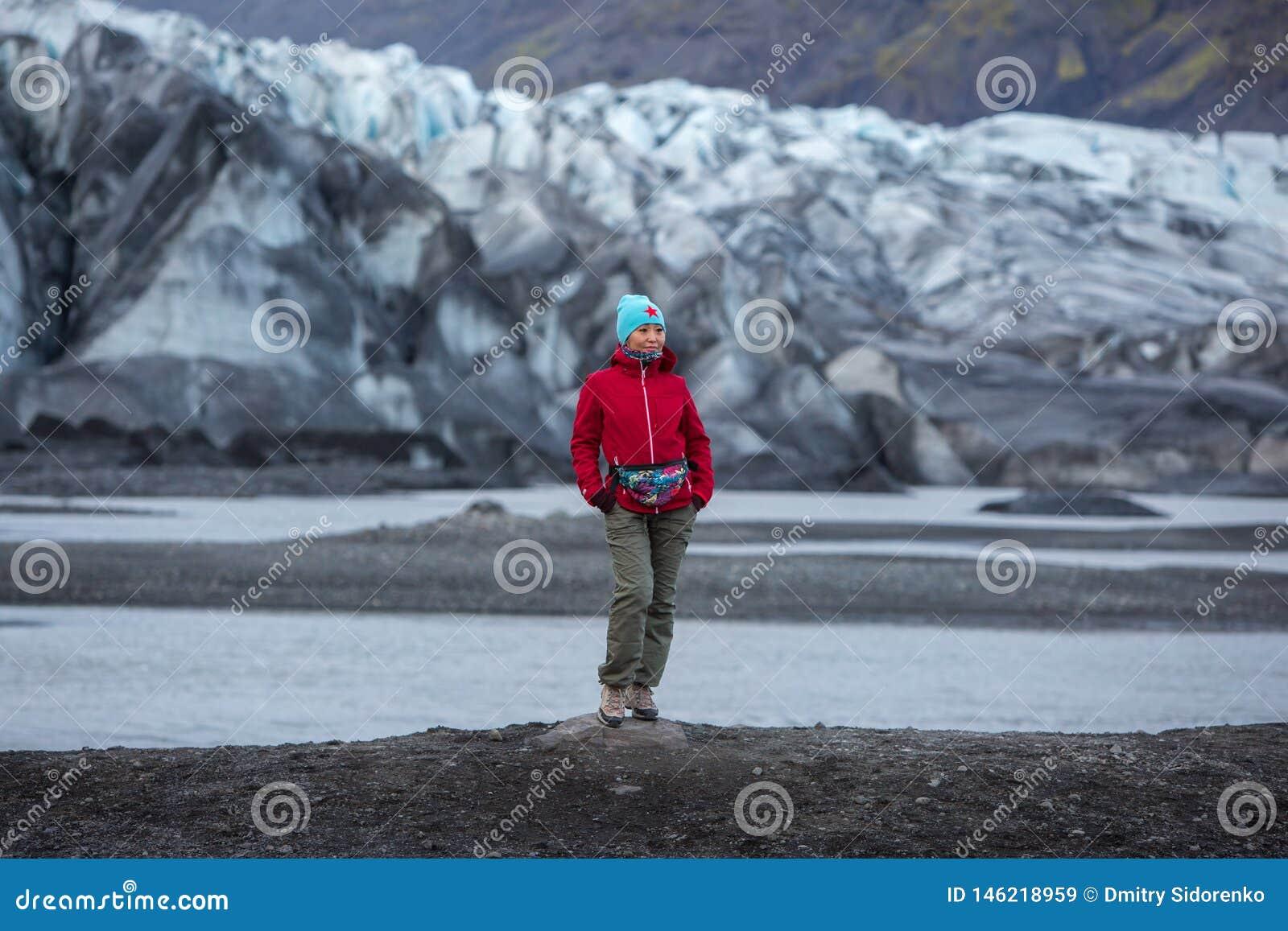 一件红色夹克的女孩在冰川的背景站立