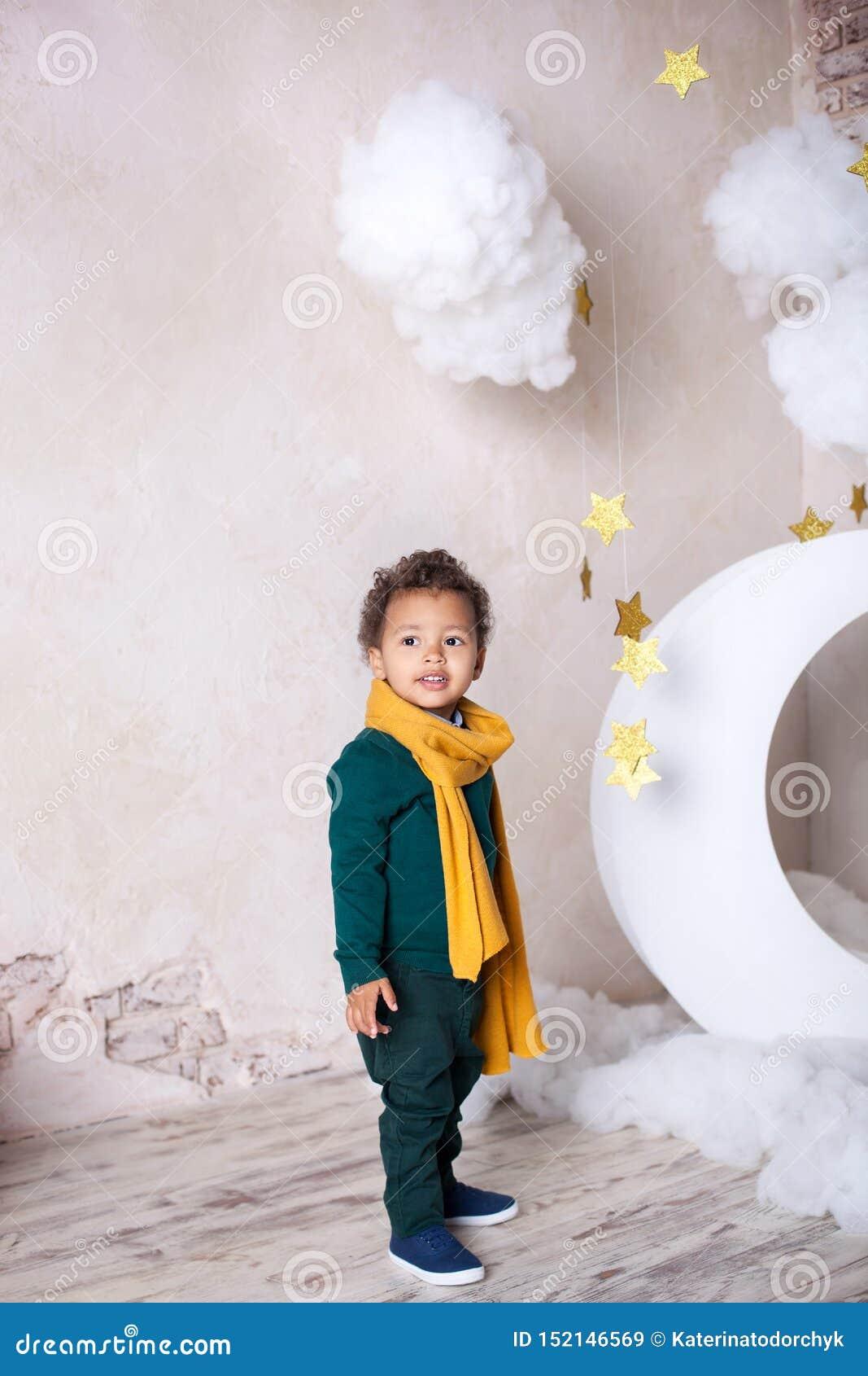 一件绿色毛线衣和一黄色围巾微笑的黑人男孩 小的非裔美国人的画象 o 黑人男孩站立ne