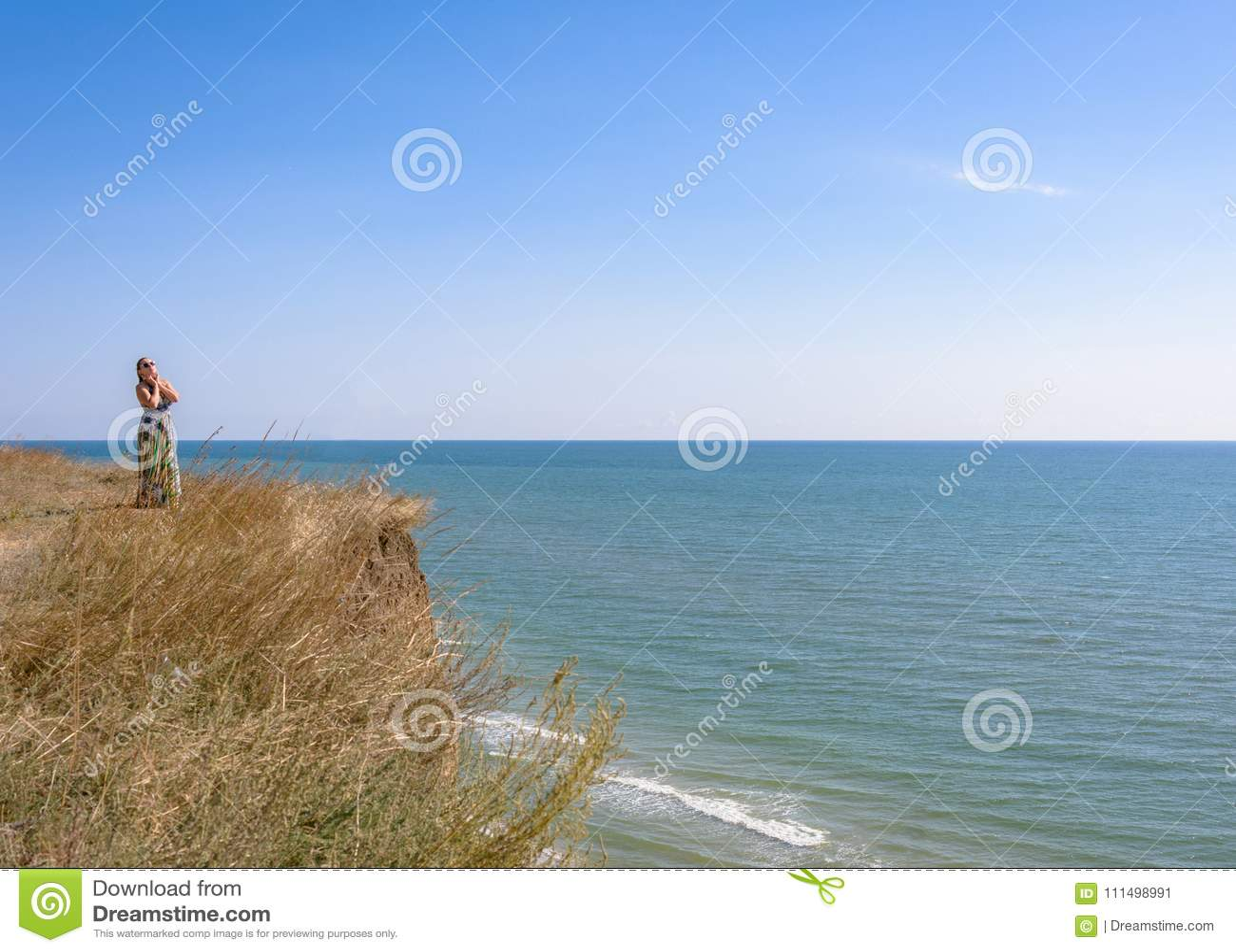 一件绿色礼服的一名英俊的妇女是在高海边上