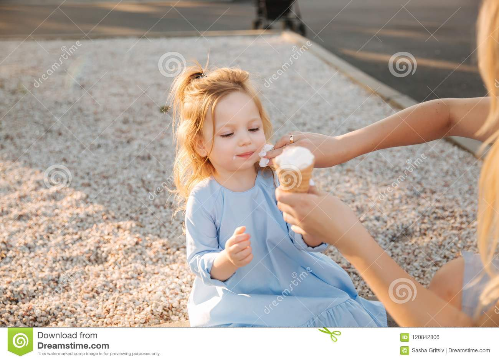 一件蓝色礼服的美丽的小女孩吃冰淇凌,妈咪的帮助并且抹她的嘴