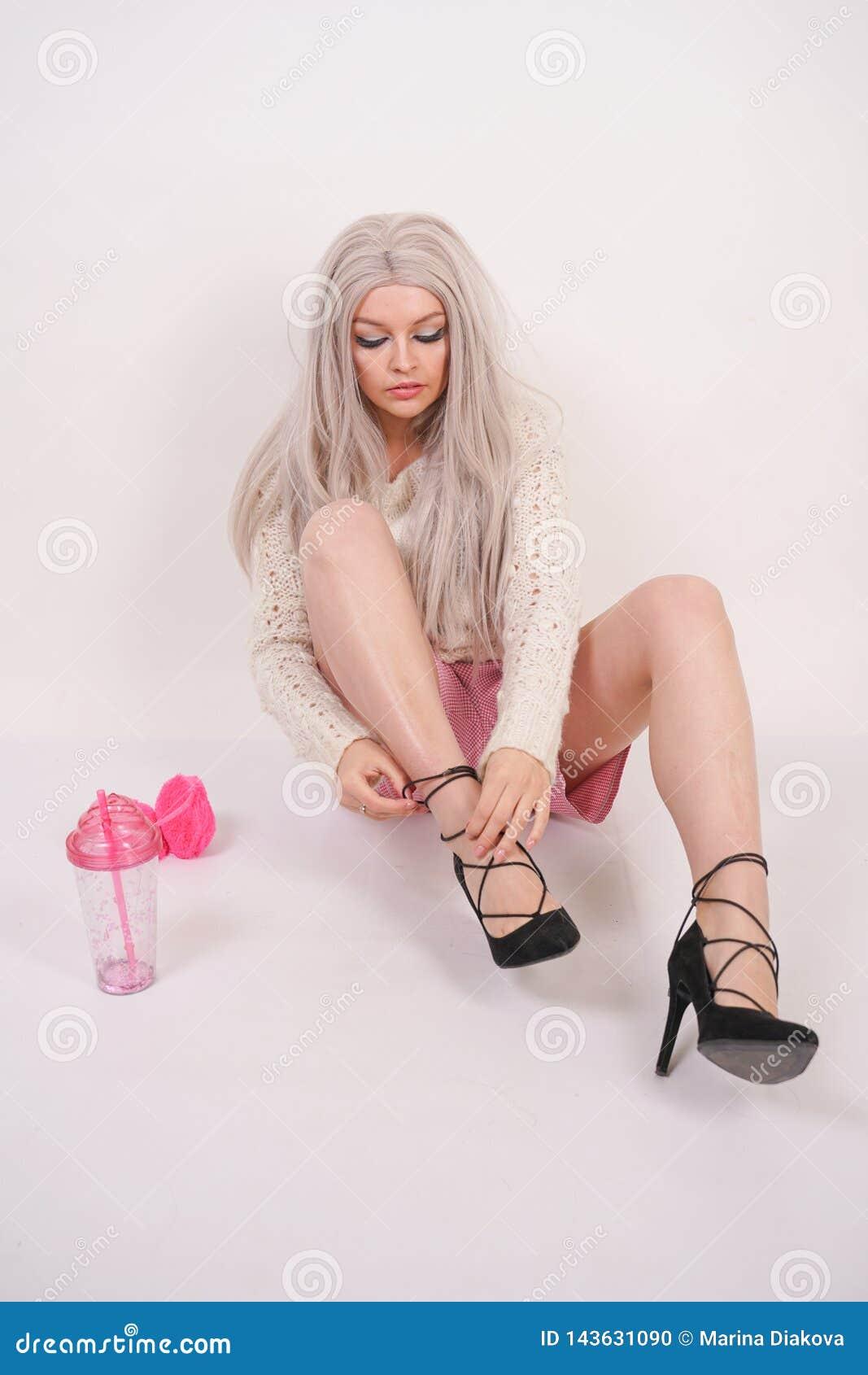 一件被编织的毛线衣的逗人喜爱的白种人年轻白肤金发的女孩坐地板和佩带的高跟鞋黑色鞋子在她的脚在whi
