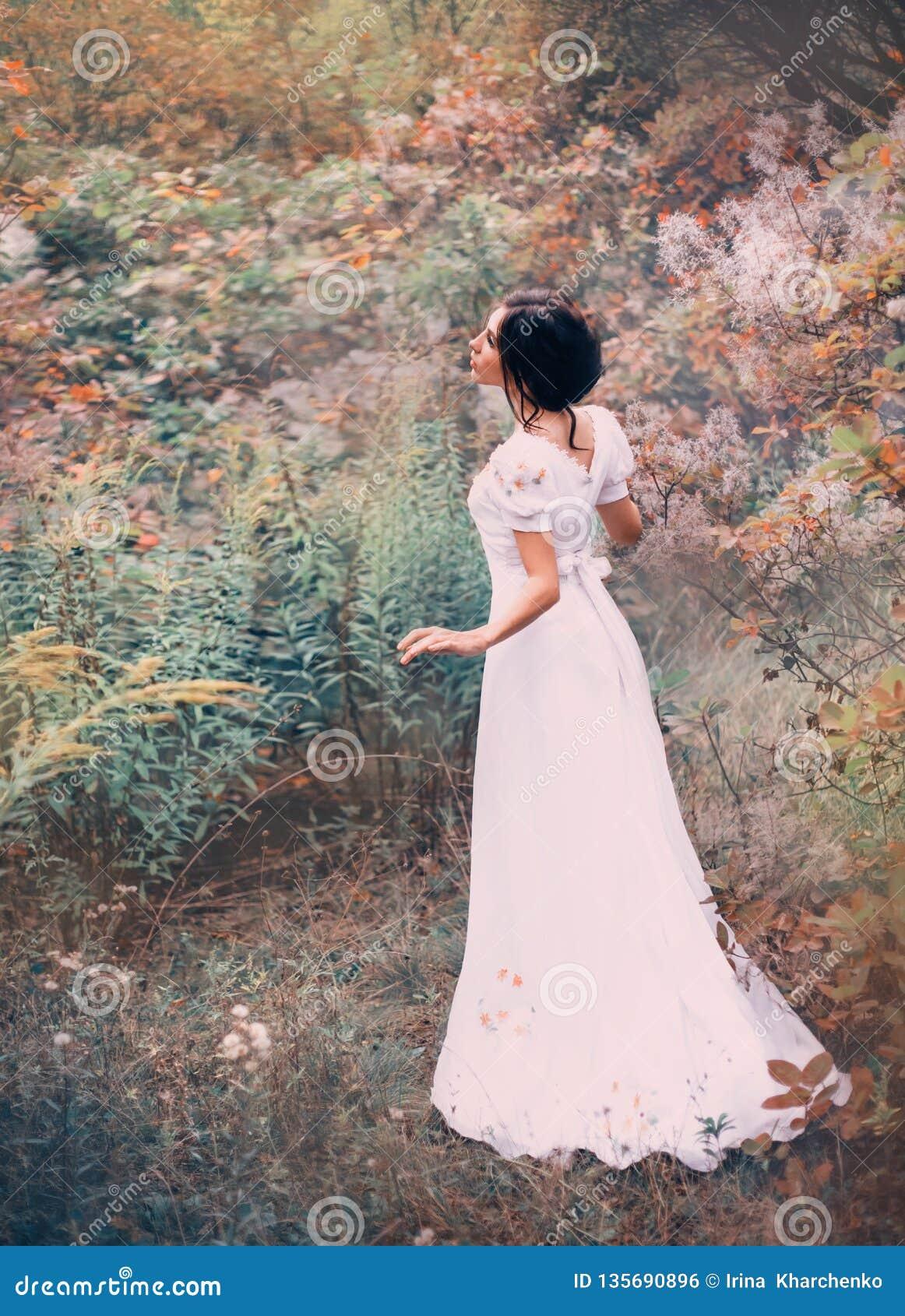一件长的白色礼服的令人愉快的公主在一个遥远的森林里得到丢失,听噪声和唱歌鸟