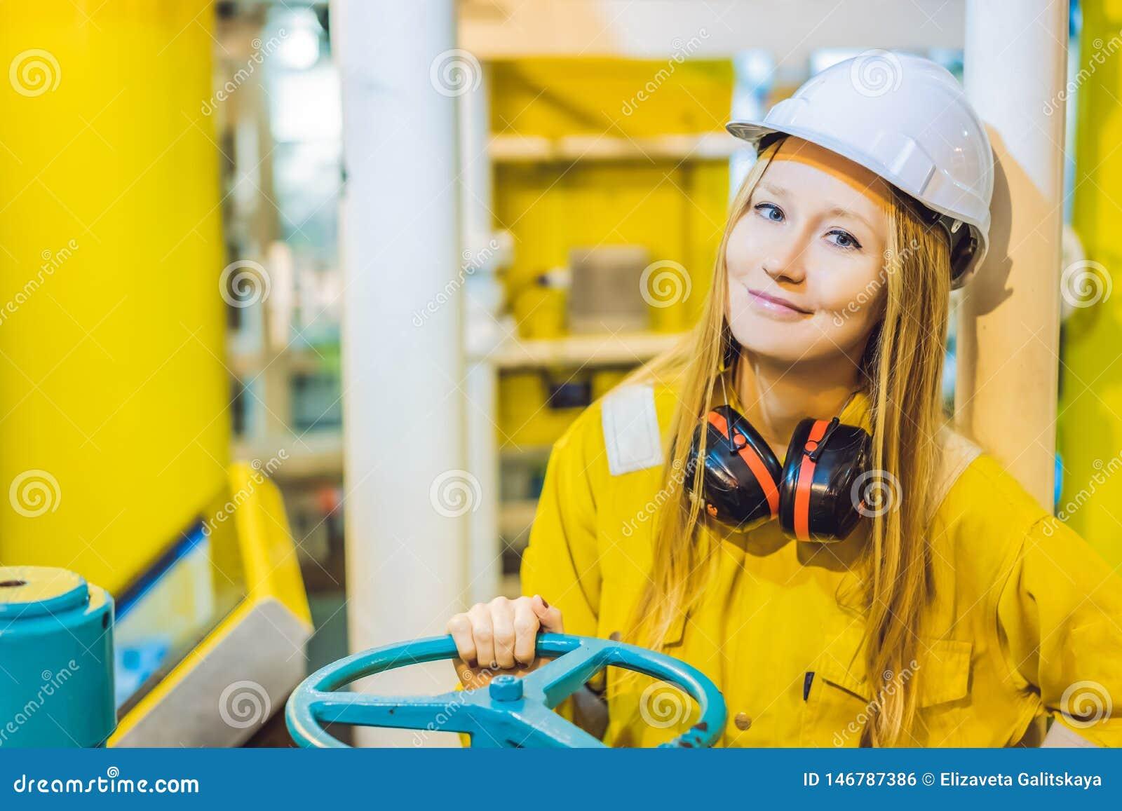 一件黄色工作制服的年轻女人、玻璃和盔甲在产业环境里,石油平台或者液化气植物