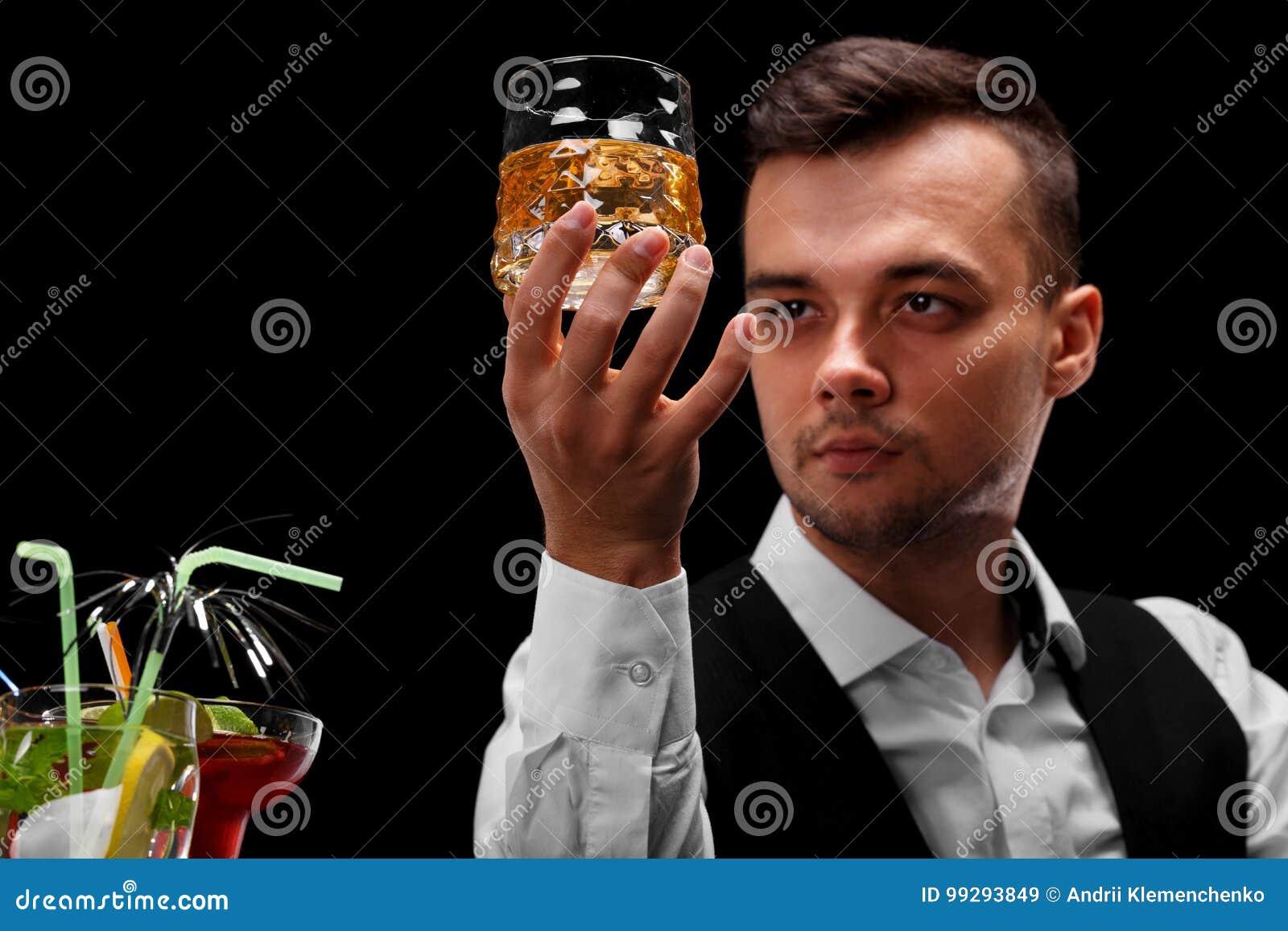一位可爱的侍酒者拿着一杯威士忌酒,在一个酒吧柜台的玛格丽塔酒玻璃在黑背景