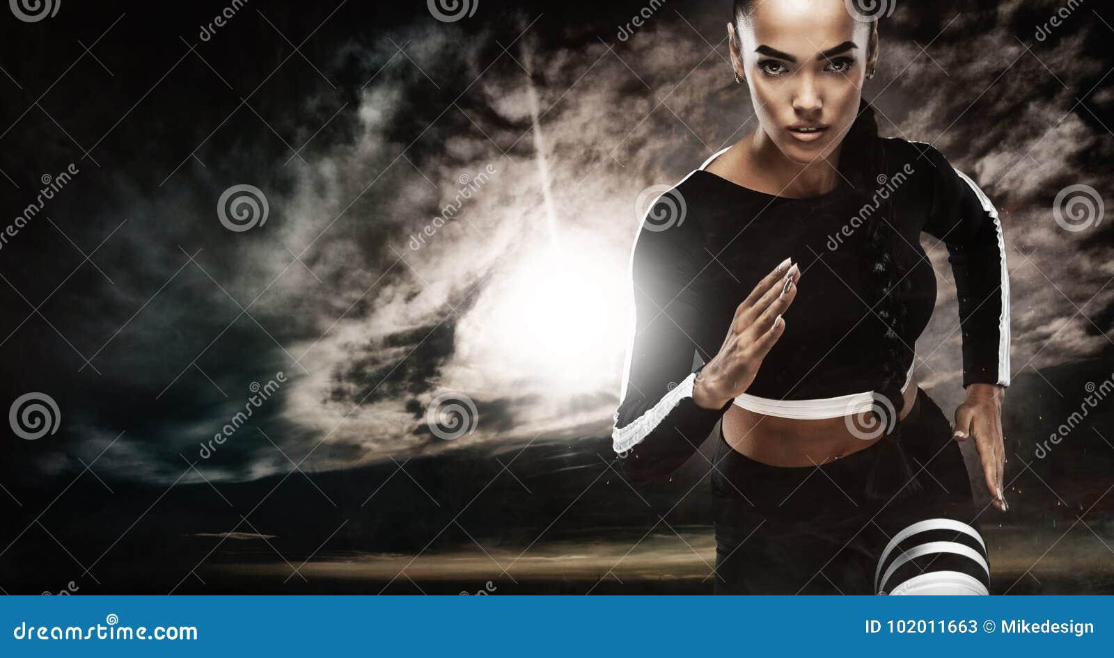 一位坚强的运动,女性短跑选手,跑在佩带在运动服、健身和体育刺激概念的日出