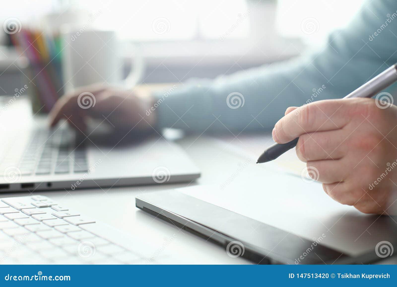 一位年轻设计师拿着从一种片剂的一支笔在他的