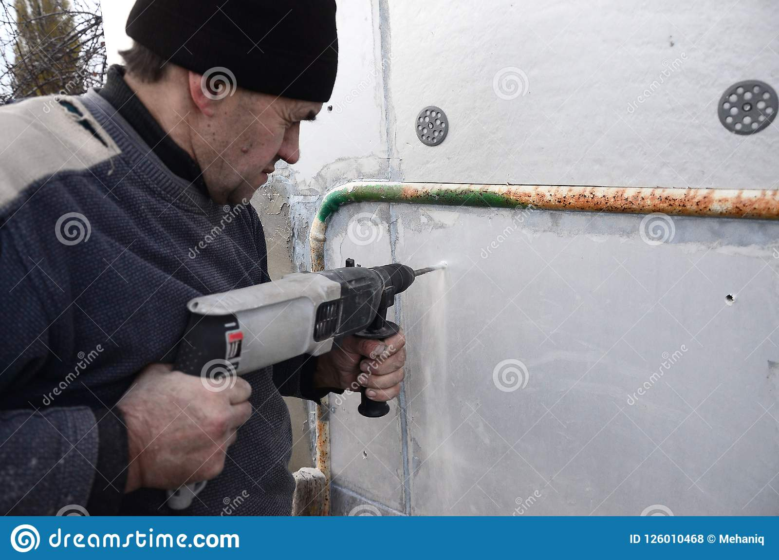 一位年长工作员操练在聚苯乙烯泡沫塑料墙壁的一个孔塑料加强的定缝销钉的随后设施的
