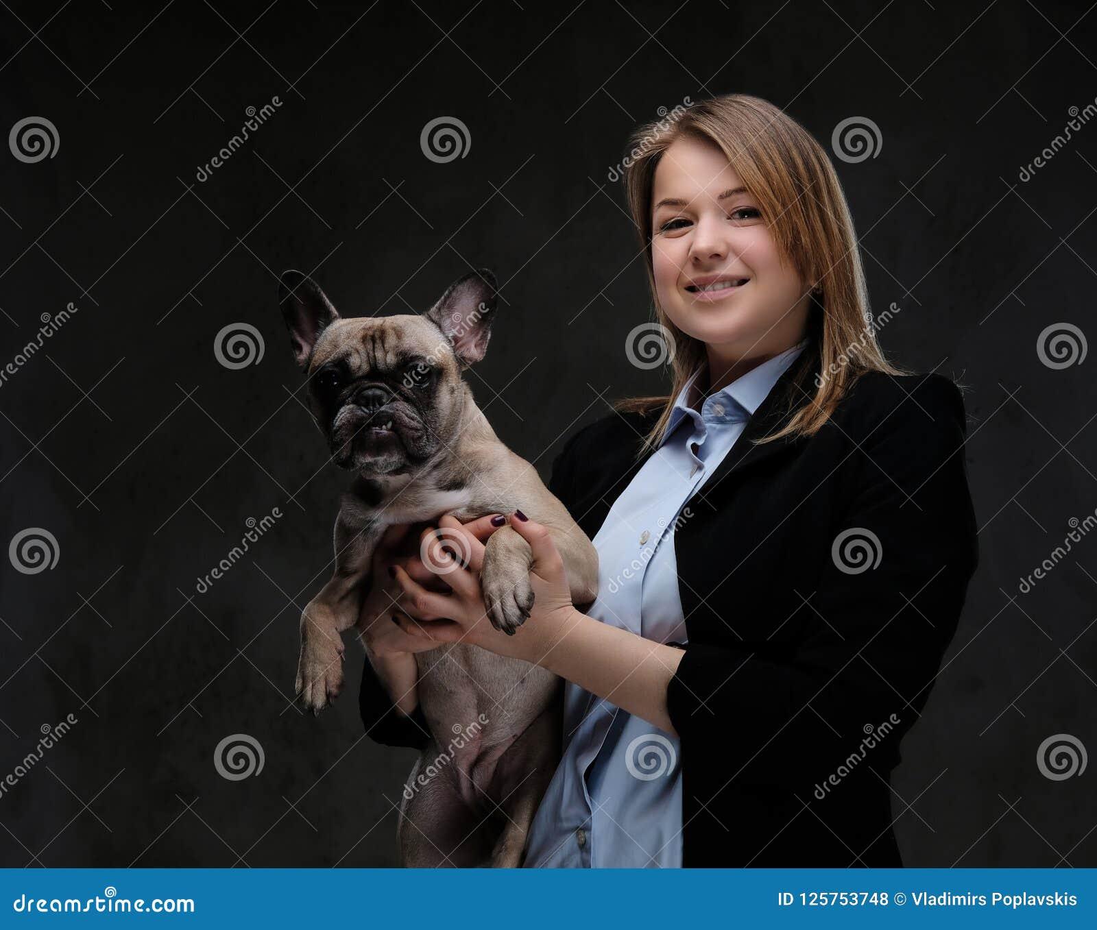 一位微笑的白肤金发的妇女交配动物者的画象拿着她逗人喜爱的哈巴狗 隔绝在黑暗的织地不很细背景