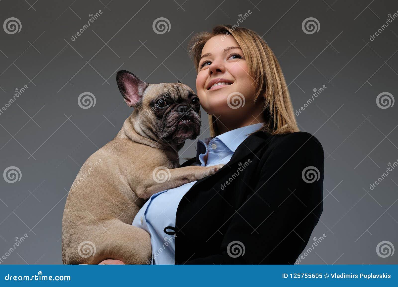 一位愉快的白肤金发的妇女交配动物者的画象拿着她逗人喜爱的哈巴狗 查出在灰色背景
