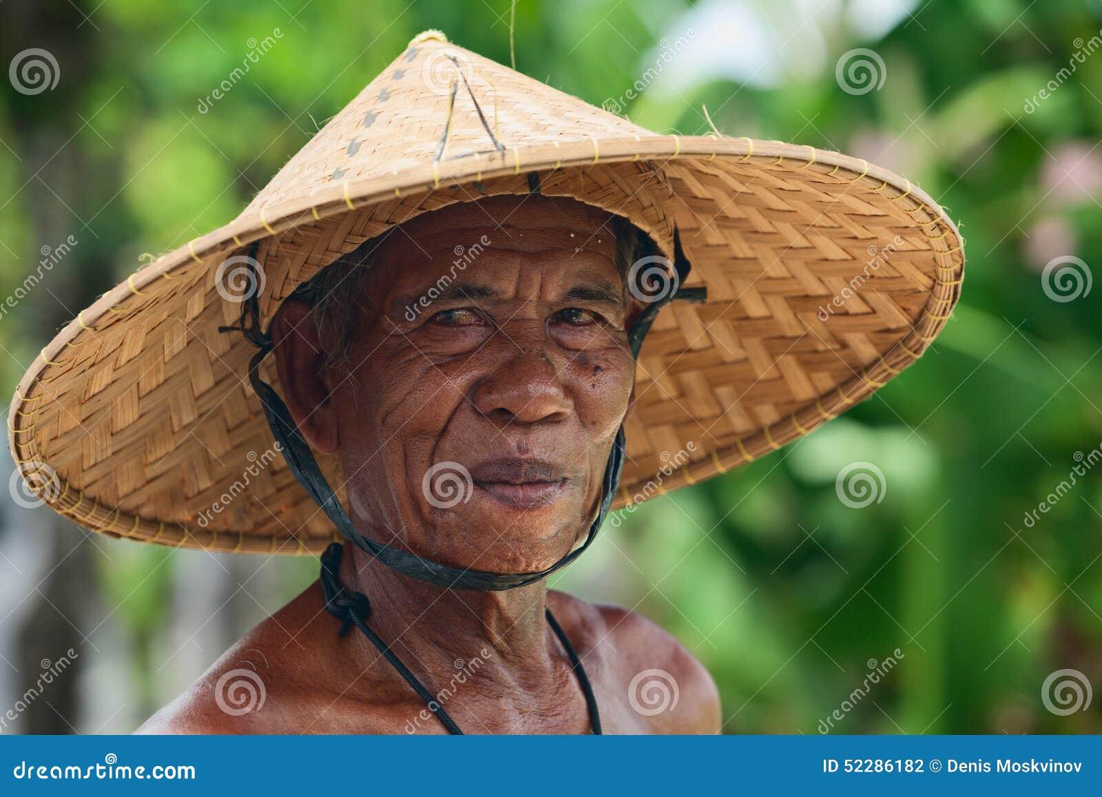 农夫帽子_农夫的画象有一张起皱纹的面孔的在传统秸杆宽充满帽子在收获在米大