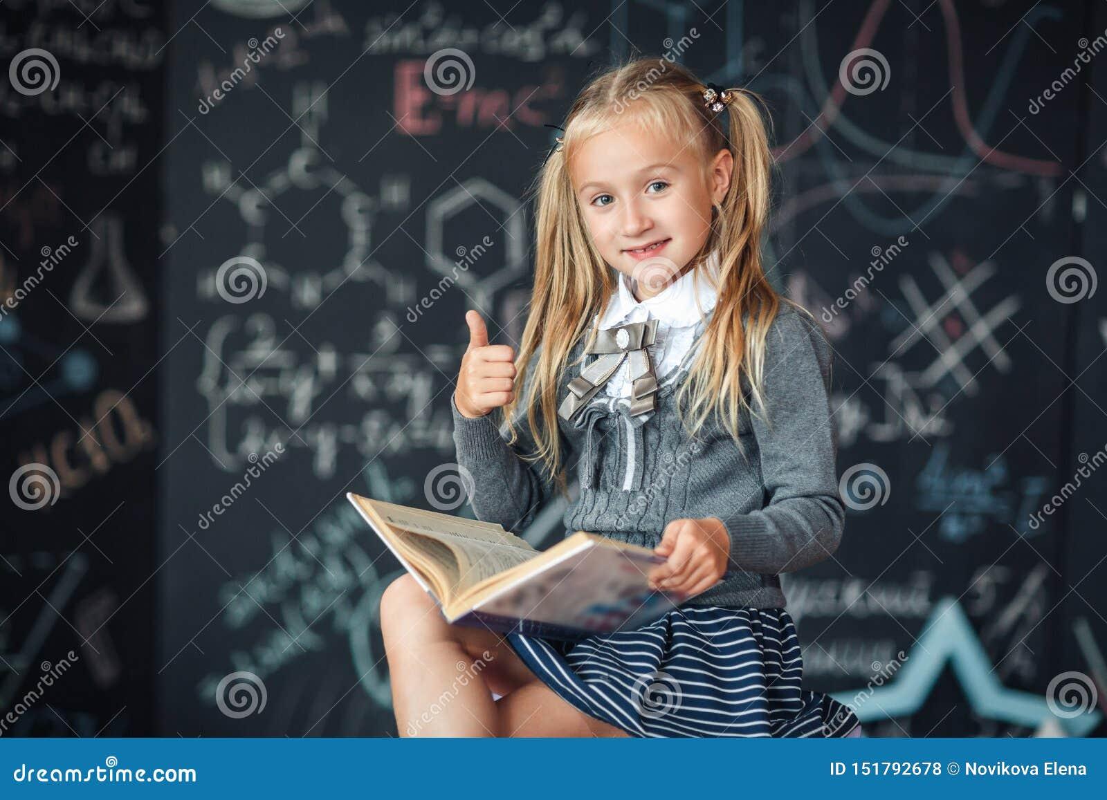一位甜女孩女小学生坐一个黑板有学校惯例背景 工作家庭作业在读书旁边并且显示拇指