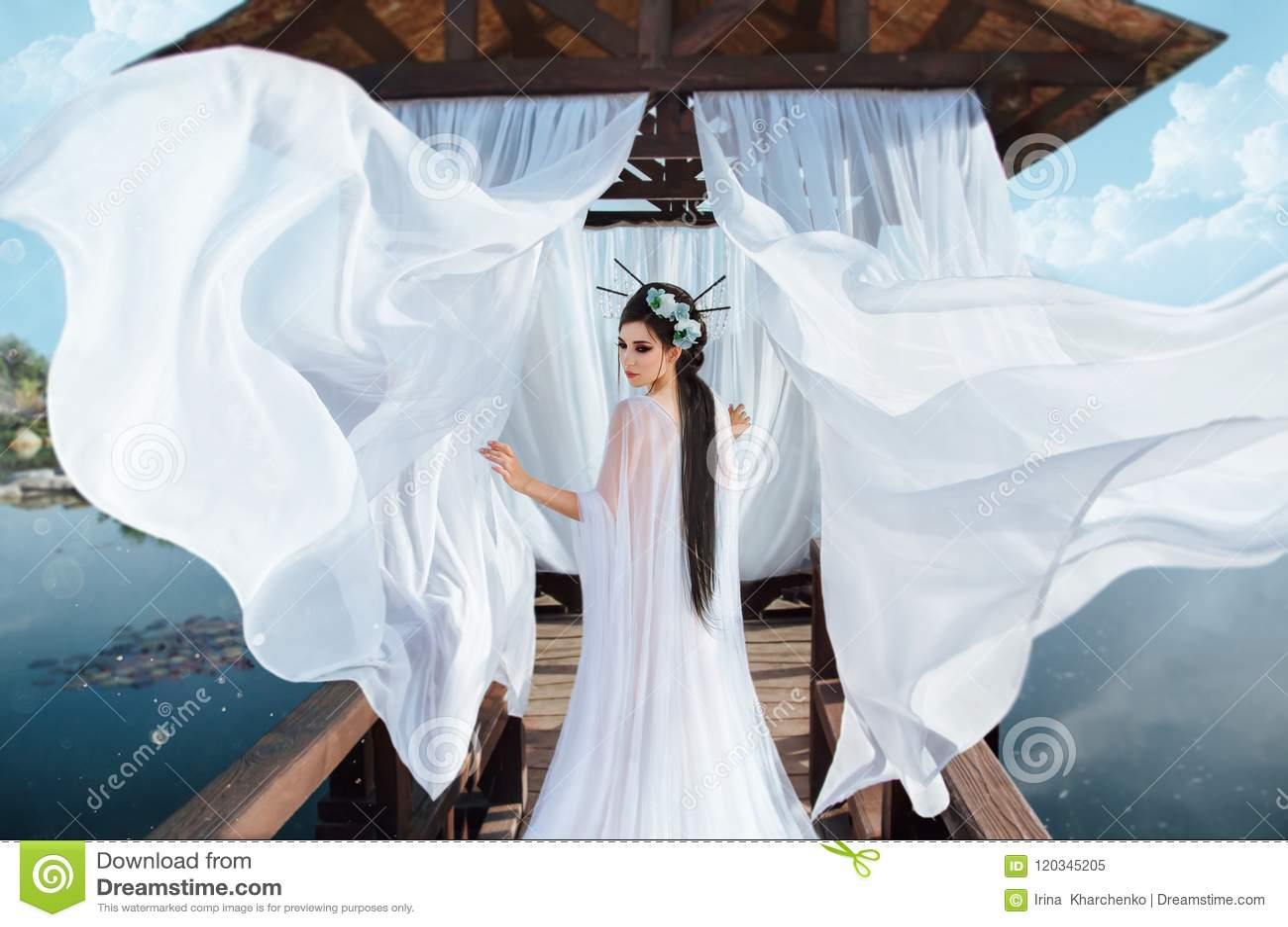 一位美丽的女巫在一个木眺望台的背景站立在水旁边,与一件白色空气礼服 在图片