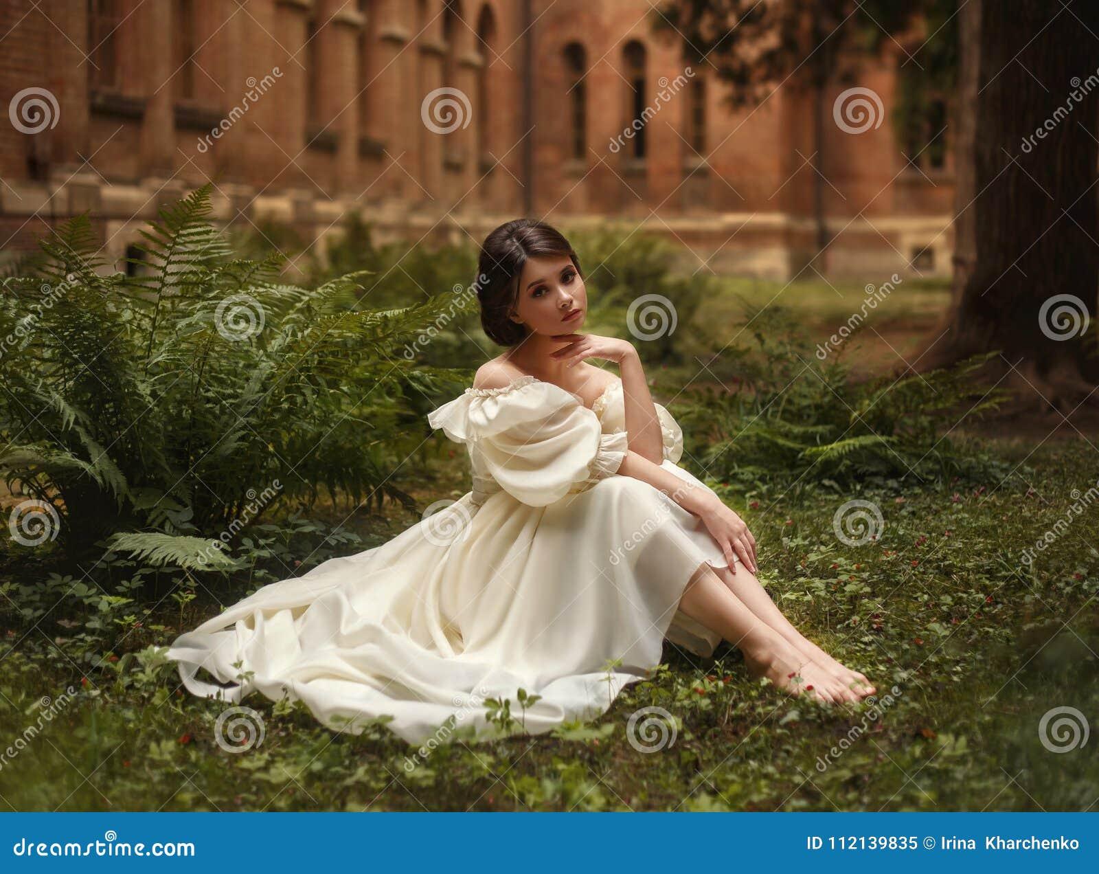 一位难以置信地美丽的公主在蕨和青苔中的城堡庭院里坐 一张美妙地幼稚面孔和