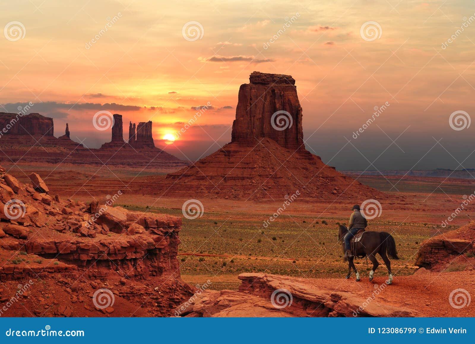 一匹马的一位牛仔在日落在犹他亚利桑那边界的,美国纪念碑谷部族公园