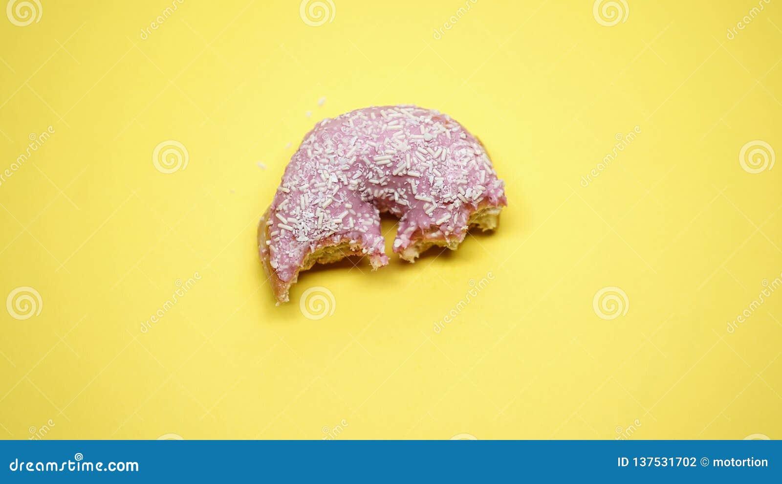一半在黄色背景、垃圾食品和不健康的饮食,宏观射击的被吃的多福饼