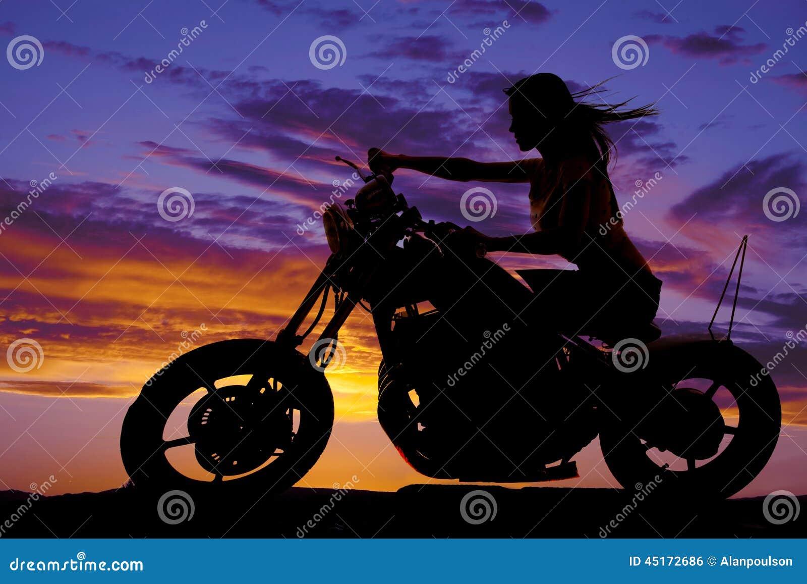 一名妇女的剪影摩托车风吹的